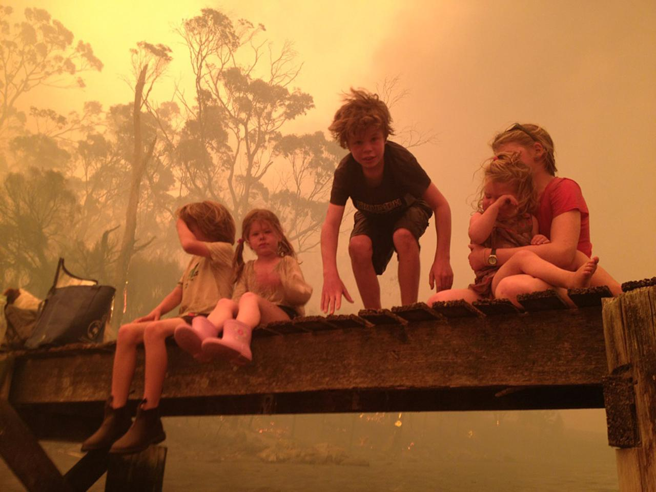 In this Jan. 4, 2013, photo provided by the Holmes family, the Walker siblings six-year-old Caleb, left, four-year-old Esther, second from left, nine-year-old Liam, and eleven-year-old Matilda, right, holding two-year-old Charlotte, prepare to enter the water to take refuge with their grandparents under a jetty as a wildfire rages nearby in the Tasmanian town of Dunalley, east of the state capital of Hobart, Australia. The family credits God with their survival from the fire that destroyed around 90 homes in Dunalley. Record temperatures across southern Australia cooled Wednesday, Jan. 9, 2013, reducing the danger from scores of raging wildfires but likely bringing only a brief reprieve from the summer's extreme heat and fire risk. (AP Photo/The Holms Family, Tim Holmes) EDITORIAL USE ONLY
