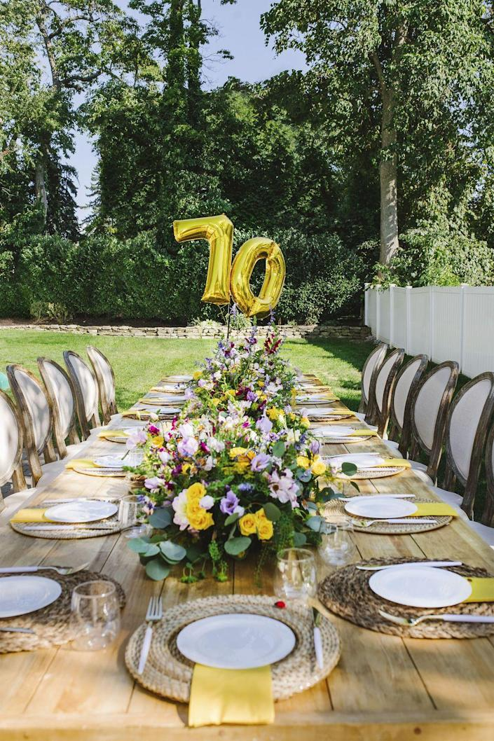 """<p>A top tip from Ashley Allegretta of <a href=""""https://www.ptevents.com/"""" rel=""""nofollow noopener"""" target=""""_blank"""" data-ylk=""""slk:Personal Touch Catering Experience"""" class=""""link rapid-noclick-resp"""">Personal Touch Catering Experience</a>: Bring indoor furniture outside to create a dreamy """"dining room."""" Wild centerpieces and a giant balloons finish off the look.</p>"""