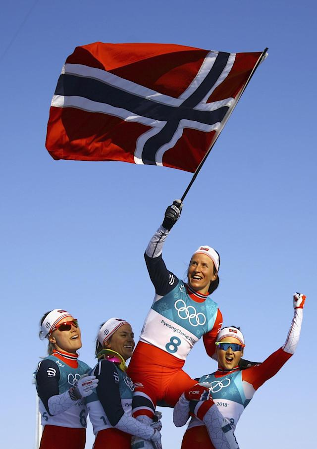 Cross-Country Skiing - Pyeongchang 2018 Winter Olympics - Women's 30km Mass Start Classic - Alpensia Cross-Country Skiing Centre - Pyeongchang, South Korea - February 25, 2018 - Winner Marit Bjoergen of Norway waves the Norwegian flag as she is carried by her teammates. REUTERS/Carlos Barria TPX IMAGES OF THE DAY