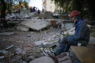 A member of rescue services rests during search operations in the debris of a collapsed building for survivors in Izmir, Turkey, Sunday, Nov. 1, 2020. Rescue teams continue ploughing through concrete blocs and debris of collapsed buildings in Turkey's third largest city in search of survivors of a powerful earthquake that struck Turkey's Aegean coast and north of the Greek island of Samos, Friday Oct. 30, killing dozens Hundreds of others were injured.(AP Photo/Emrah Gurel)