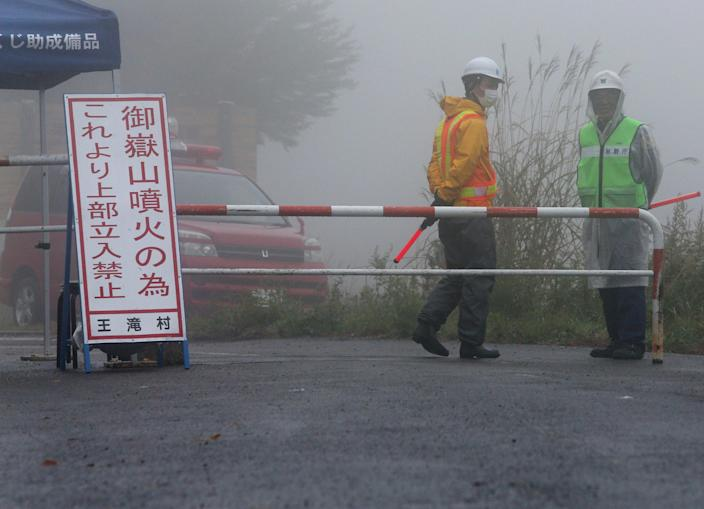 Security staff guard a closed road approacing Mount Ontake, near Otaki village in Nagano prefecture, Japan, on October 3, 2014 (AFP Photo/-)