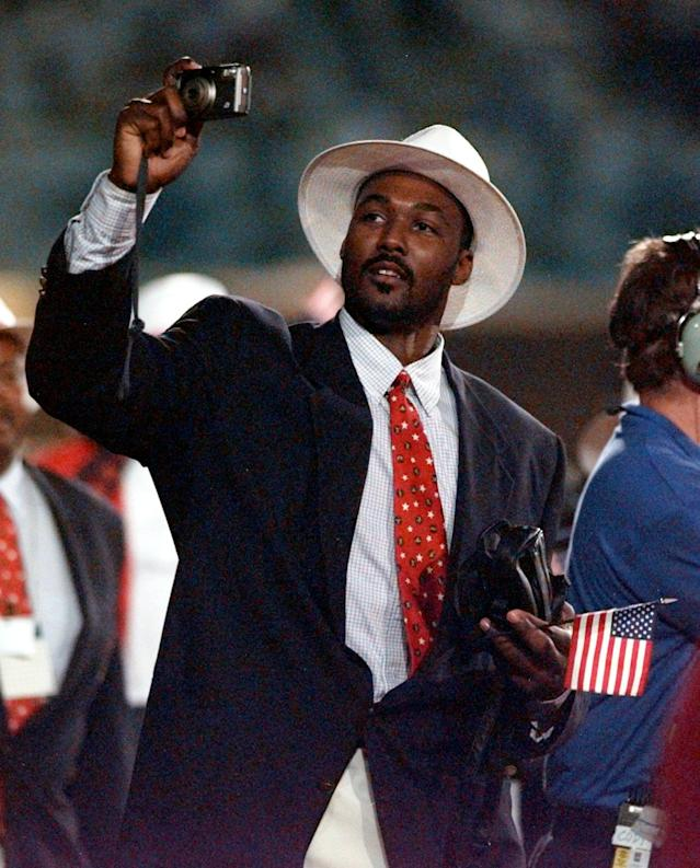 Karl Malone of the U.S. Dream Team snaps some photos as he arrives on the field during the opening ceremonies of the Summer Olympics Friday, July 19, 1996, in Atlanta. (AP Photo/Amy Sancetta)