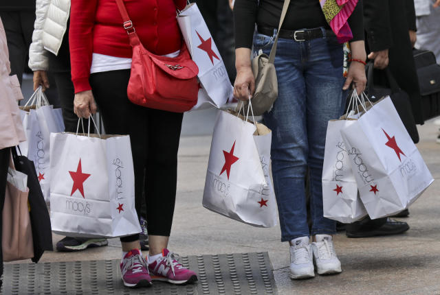 Shoppers holding bags from Macy's wait to cross an intersection in New York. Macy's Inc. reports earnings, Thursday, May 11, 2017. (AP Photo/Bebeto Matthews)