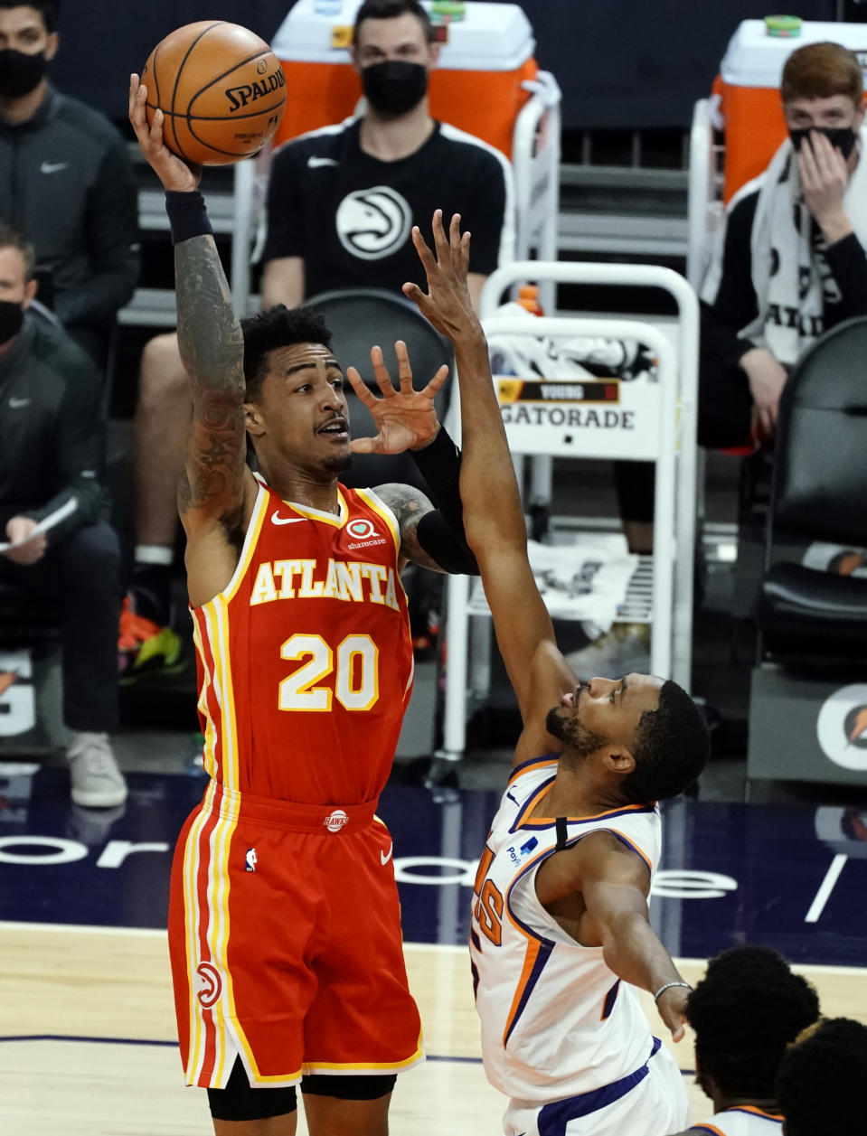 Atlanta Hawks forward John Collins (20) shoots over Phoenix Suns forward Mikal Bridges during the first half of an NBA basketball game Tuesday, March 30, 2021, in Phoenix. (AP Photo/Rick Scuteri)