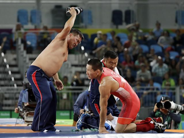 <p>Coaches for Mongolia's Mandakhnaran Ganzori, at right, strip in protest after a loss to Uzbekistan's Ikhtiyor Navruzov during the men's 65-kg freestyle bronze medal wrestling match at the 2016 Summer Olympics in Rio de Janeiro, Brazil, Saturday, Aug. 20, 2016. (AP) </p>