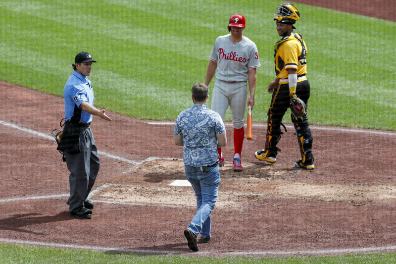 Home plate umpire Ben May, left, looks at a man walking towards Pittsburgh Pirates catcher Elias Diaz, right and Philadelphia Phillies' Brad Miller as he comes to bat in the sixth inning of a baseball game, Sunday, July 21, 2019, in Pittsburgh. The police took the man from the field and play continued. (AP Photo/Keith Srakocic)