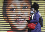 <p>A woman wears protective face coverings as she passes the shutters of a closed shop in West Ealing in London, Thursday, Feb. 25, 2021. It has been announced that further testing of residents in the London Borough of Ealing will be carried out after additional cases of the coronavirus variant first identified in South Africa were detected. (AP Photo/Kirsty Wigglesworth)</p>