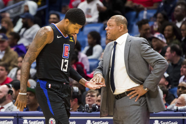 Los Angeles Clippers forward Paul George (13) taps the hand of Clippers head coach Doc Rivers as he walks to the bench in the second half of an NBA basketball game against the New Orleans Pelicans in New Orleans, Thursday, Nov. 14, 2019. (AP Photo/Sophia Germer)