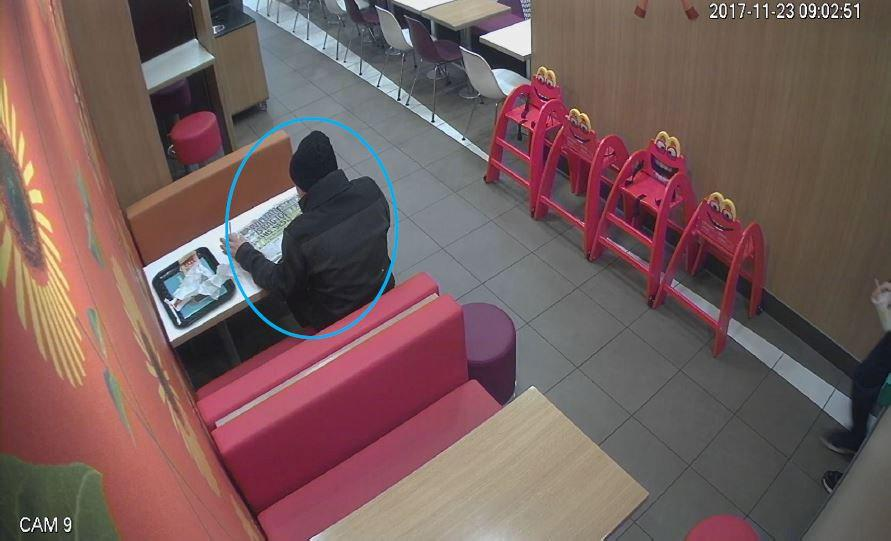 He was seen on CCTV enjoying a McDonald's meal while reading the paper (SWNS)