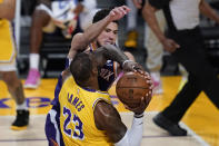 Phoenix Suns guard Devin Booker (1) defends against Los Angeles Lakers forward LeBron James (23) during the second quarter of Game 6 of an NBA basketball first-round playoff series Thursday, Jun 3, 2021, in Los Angeles. (AP Photo/Ashley Landis)