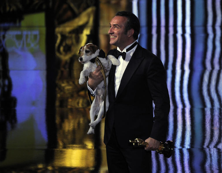 "Jean Dujardin holds Uggie after accepting the Oscar for best picture for ""The Artist"" during the 84th Academy Awards on Sunday, Feb. 26, 2012, in the Hollywood section of Los Angeles. (AP Photo/Mark J. Terrill)"