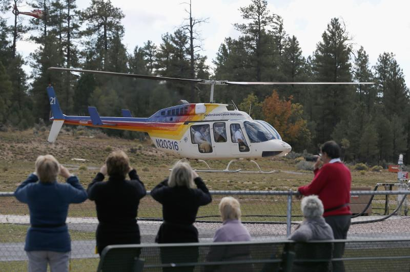 Hundreds of tourists flock to Grand Canyon Airport to take helicopter and plane tours as the only way they could see the Grand Canyon as the entrance to Grand Canyon National Park remains closed to visitors due to the continued federal government shutdown on Friday Oct. 11, 2013, in Tusayan, Ariz. (AP Photo/Ross D. Franklin)