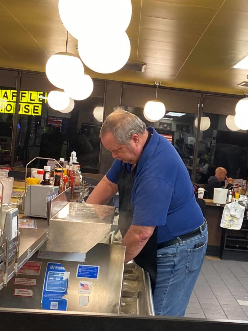 A man in a blue shirt washes dishes at an Alabama Waffle house chain when staff failed to show up.
