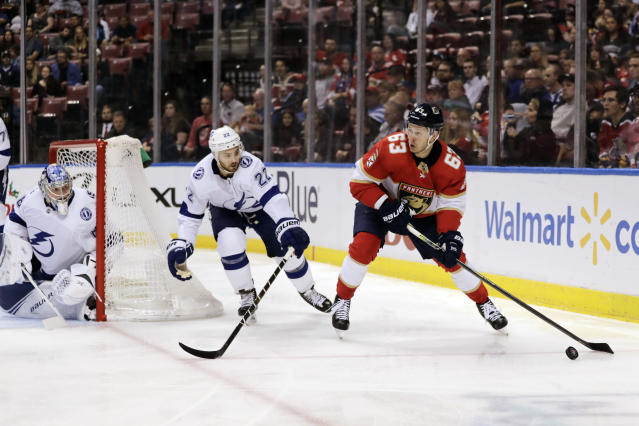 Florida Panthers' Evgenii Dadonov (63) moves the puck as Tampa Bay Lightning goalkeeper Andrei Vasilevskiy, left, and Kevin Shattenkirk (22) defend during the second period of an NHL hockey game, Tuesday, Dec. 10, 2019, in Sunrise, Fla. (AP Photo/Luis M. Alvarez)