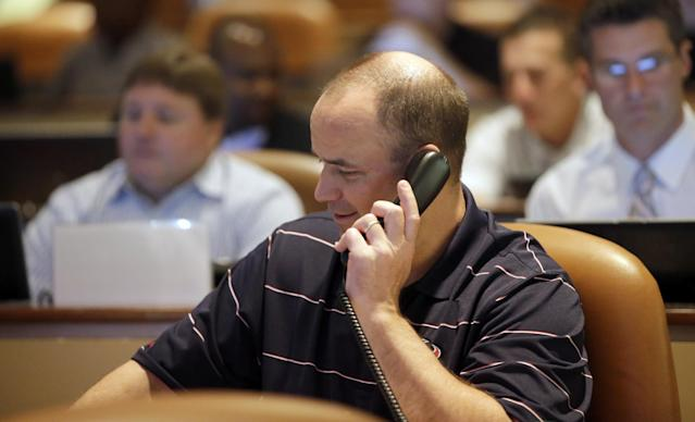 Houston Texans coach Bill O'Brien holds a phone to his ear as he sits in the Texans daft war room Thursday, May 8, 2014, in Houston. The Texans have the first pick in the NFL draft. (AP Photo/David J. Phillip)