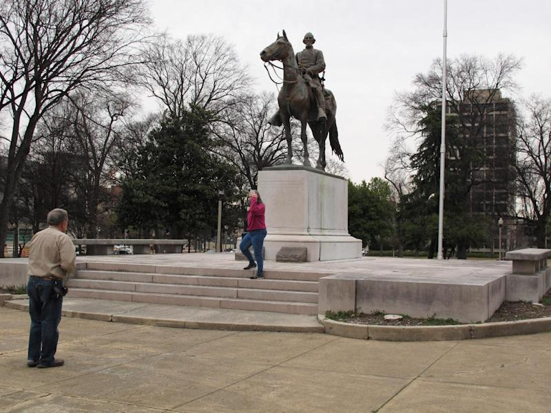 In this Wednesday, Feb. 6, 2013 photo, visitors take pictures of a statue of Nathan Bedford Forrest on his horse at a park named after the confederate cavalryman in Memphis Tenn. The Memphis City Council has voted to rename Forrest Park and two other Confederate-themed parks. (AP Photo/Adrian Sainz)