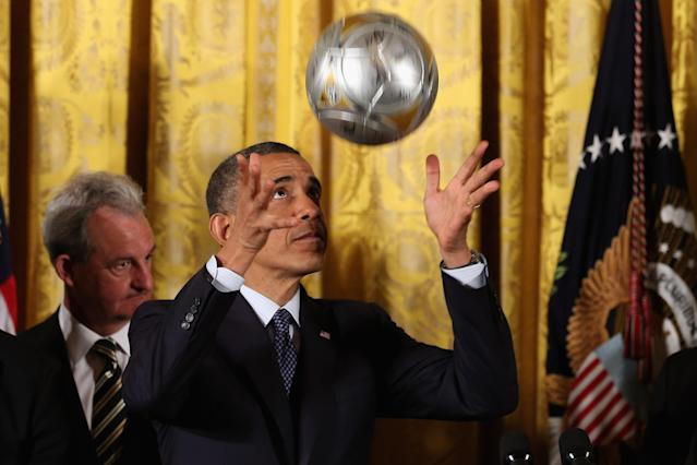 "WASHINGTON, DC - MARCH 26: U.S. President Barack Obama throws a ball into the air before bouncing a soccer ball on his head during a ceremony honoring players and coaches from the National Hockey League Stanley Cup-winning Los Angeles Kings and the Major League Soccer champions Los Angeles Galaxy in the East Room of the White House March 26, 2013 in Washington, DC. After the White House honors both California teams, players will participate in a question-and-answer panel with Sam Kass, Assistant White House Chef and Executive Director of first lady Michelle Obama's health program ""Let's Move!"" (Photo by Chip Somodevilla/Getty Images)"