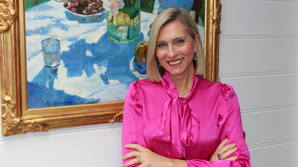 Investor Danielle Ecuyer stands in front of a painting while smiling.