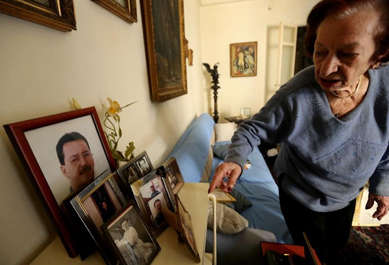 Marie Mansourati, 83, adjusts pictures of her kidnapped son Dani, more than two decades after he was taken by Syrian troops to Damascus, at her house in Beirut on April 8, 2015 (AFP Photo/Joseph Eid)