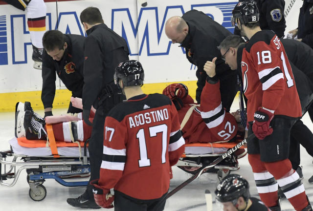 New Jersey Devils defenseman Mirco Mueller gives a thumbs-up sign as he is wheeled off the ice on a stretcher after being injured during the third period of an NHL hockey game against the Calgary Flames Wednesday, Feb. 27, 2019, in Newark, N.J. The Flames defeated the Devils 2-1.(AP Photo/Bill Kostroun)