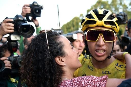 Egan Bernal, wearing the overall leader's yellow jersey, is congratulated by his girlfriend Xiomy Guerrero
