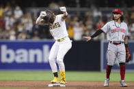 San Diego Padres' Fernando Tatis Jr., left, dances at second base in front of Cincinnati Reds' Jonathan India (6) after hitting a double during the third inning of a baseball game Friday, June 18, 2021, in San Diego. (AP Photo/Derrick Tuskan)