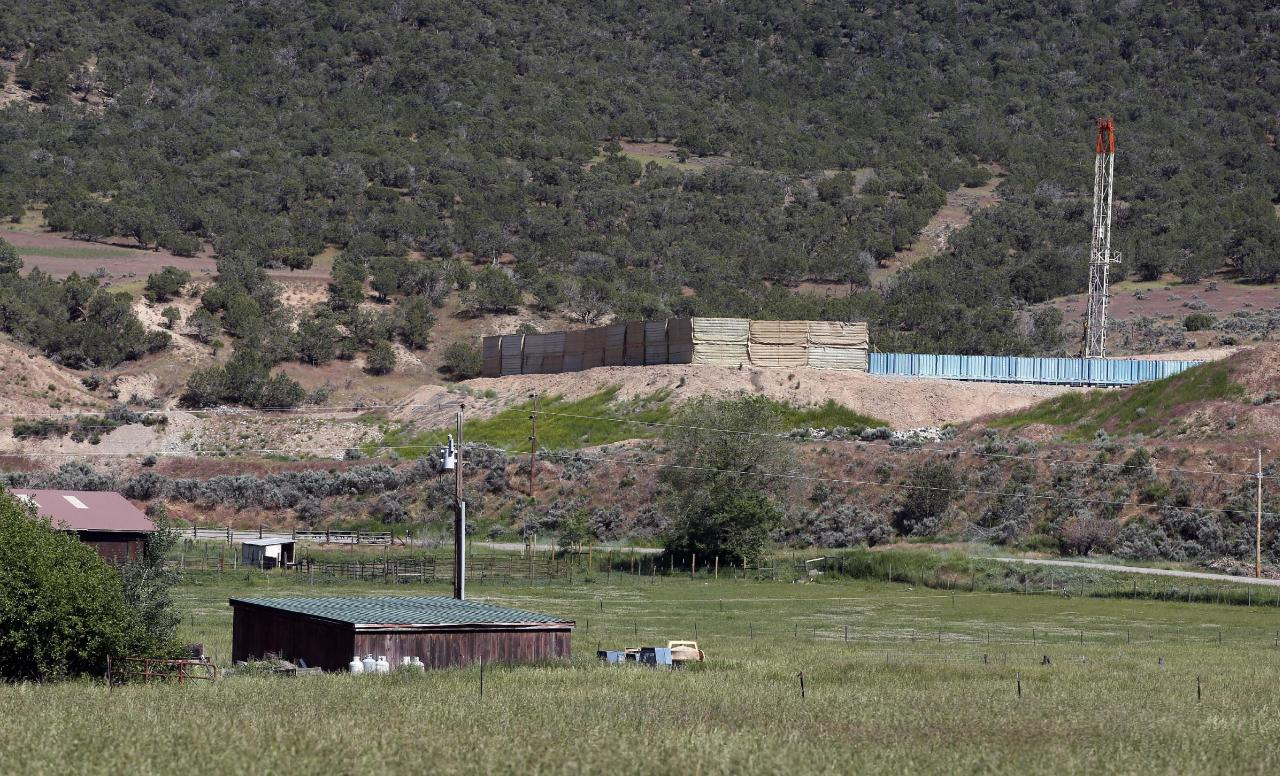 In this June 9, 2014 photo, an oil and gas rig on a well pad is visible at right, adjacent to a ranch in New Castle, a small farming and ranching settlement on the Western Slope of the Rockies, in Colo. Four in 10 new oil and gas wells near national forests and fragile watersheds or otherwise identified as higher pollution risks escape federal inspection, unchecked by an agency struggling to keep pace with America's drilling boom, according to an Associated Press review that shows wide state-by-state disparities in safety checks. (AP Photo/Brennan Linsley)