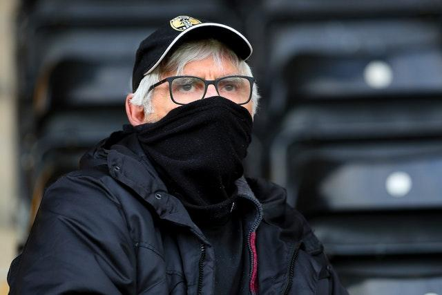 A Notts County fan covers his mouth with a scarf