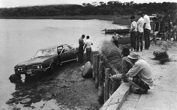 Spectators look on as police work near the car driven by Sen. Edward Kennedy of Massachusetts which plunged off a bridge in an island pond on July 19, 1969, Chappaquiddick Island near Edgartown, Martha's Vineyard, Mass. (Photo: Bettmann/Getty Images)