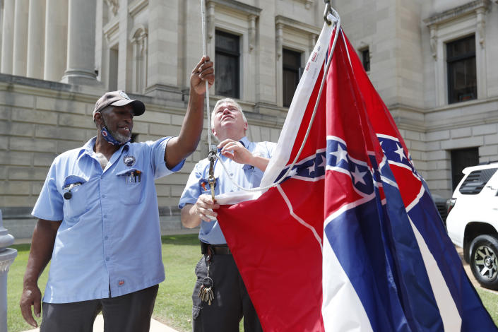 Mississippi Department of Finance and Administration employees Willie Townsend, left, and Joe Brown, attach a couple of Mississippi state flags to the harness before raising them over the Capitol grounds in Jackson, Miss., Tuesday, June 30, 2020. The two men raised about 100 flags, provided by the Secretary of State's office, for people or organizations that purchased a state flag that flew over the grounds. Gov. Tate Reeves will sign a bill that evening retiring the last state flag with the Confederate battle emblem during a ceremony at the Governor's Mansion. Upon the governor signing the bill, the flag will lose its official status. (AP Photo/Rogelio V. Solis)