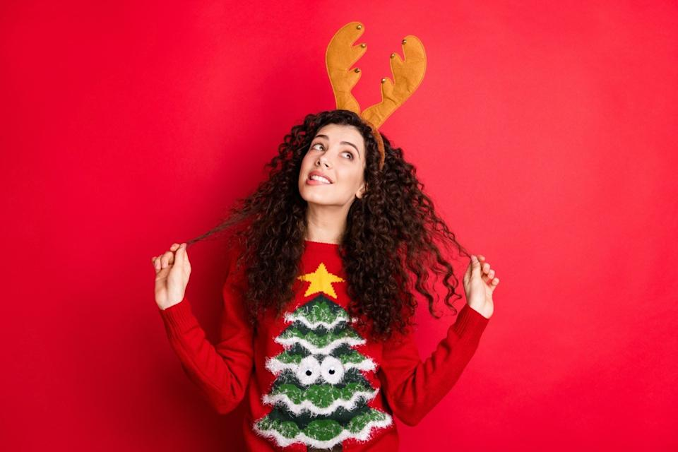 Young woman in Christmas tree sweater and reindeer antlers