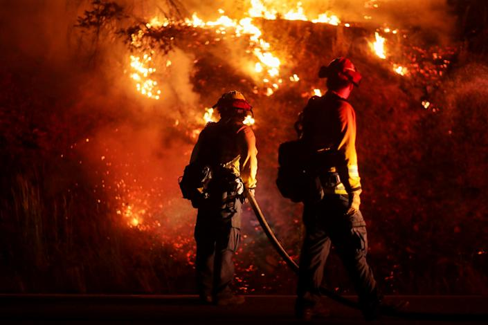 Firefighters extinguish spot fires along Route 89 Dixie Fire in Moccasin, now over 200,000 acres, California, U.S., July 28, 2021.  REUTERS/David Swanson     TPX IMAGES OF THE DAY