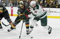 Vegas Golden Knights right wing Ryan Reaves (75) and Minnesota Wild defenseman Carson Soucy (21) vie for the puck during the second period of an NHL hockey game Monday, March 1, 2021, in Las Vegas. (AP Photo/John Locher)