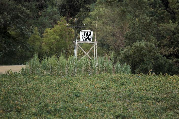 """In this May 23, 2013 photo, a water tank displays a message that reads; """"No Pascua-Lama"""" in El Corral, a small town of about 200 inhabitants, mostly from the Diaguita ethnic group, near the facilities of Barrick Gold Corp's Pascua-Lama project in northern Chile. The Diaguitas live in the foothills of the Andes, where for as long as anyone can remember they've drunk straight from the glacier-fed river that irrigates their orchards and vineyards with clean water. But since the Barrick gold mine project moved in, residents claim the river levels have dropped and some complain of cancerous growths and aching stomachs. (AP Photo/Jorge Saenz)"""