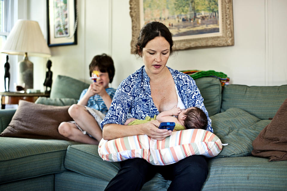 Mother breast feeding while texting on smart phone, while oder son is playing.