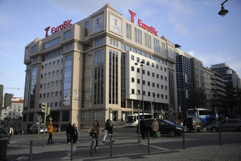 People walk past the building of Lisbon-based bank EuroBic in Lisbon, Thursday, Jan. 23, 2020. The head of private banking at EuroBic, who was named in a major Angolan money-laundering and corruption scandal, has died in an apparent suicide at home in Lisbon, police said Thursday. (AP Photo/Armando Franca)