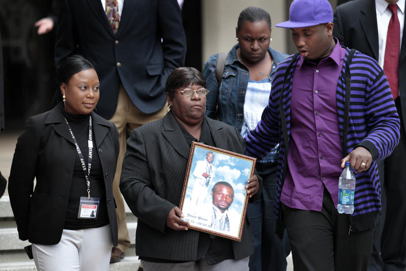 Edna Glover, second left, mother of Henry Glover, leaves Federal Court holding his photo, after the sentencing of two former New Orleans police oficers in his shooting death and burning of his body in New Orleans, Thursday, March 31, 2011. Former officer David Warren was sentenced to more than 25 years for shooting Glover without justification after Hurricane Katrina, and his ex-colleague Gregory McRae was given just over 17 years for burning the body. Right is Corey Glover, cousin of Henry, and background right is Patrice Glover, sister of Henry. (AP Photo/Gerald Herbert)