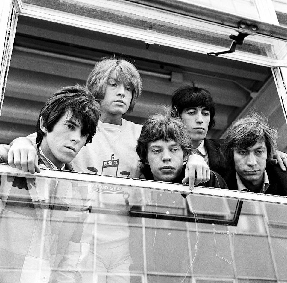 <p>Mick Jagger and the rest of his bandmates watch from a window as fans mob the Granada Studios in Manchester after their show, 1965. </p>