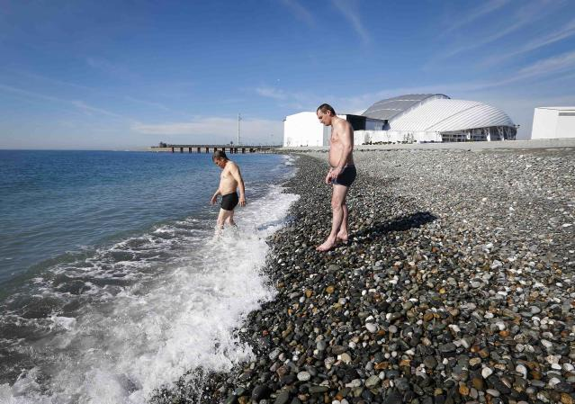 Men wade into the sea on a sunny day as the Olympic Park is seen in the background, during the 2014 Winter Olympic Games in Sochi February 12, 2014. REUTERS/Shamil Zhumatov (RUSSIA - Tags: SPORT OLYMPICS ENVIRONMENT)