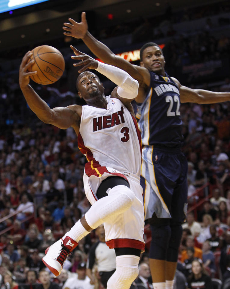 Miami Heat guard Dwyane Wade (3) goes up for a shot against Memphis Grizzlies forward Rudy Gay (22) during the first half of an NBA basketball game, Friday, April 6, 2012 in Miami. (AP Photo/Wilfredo Lee)