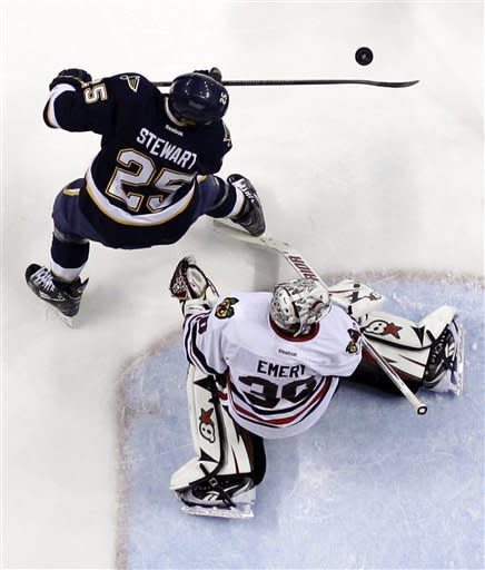 St. Louis Blues' Chris Stewart, top, tries to reach the puck as Chicago Blackhawks goalie Ray Emery defends during the second period of an NHL hockey game, Thursday, Feb. 28, 2013, in St. Louis. (AP Photo/Jeff Roberson)