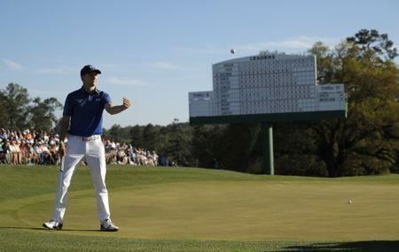 Jordan Spieth of the U.S. tosses his ball to his caddie on the 18th green in third round play during the 2017 Masters golf tournament at Augusta National Golf Club in Augusta, Georgia, U.S., April 8, 2017. REUTERS/Brian Snyder