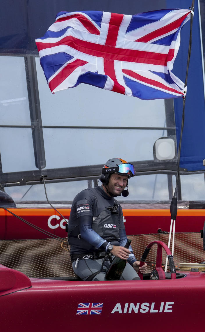 In this photo provided by SailGP, Sir Ben Ainslie holds a bottle and the Britain SailGP Team presented by INEOS remain on their F50 due to COVID-19 restrictions to celebrate their win in the final race on race Day 2 of the Bermuda SailGP event in Hamilton, Bermuda, Sunday, April 25, 2021. (Bob Martin/SailGP via AP)