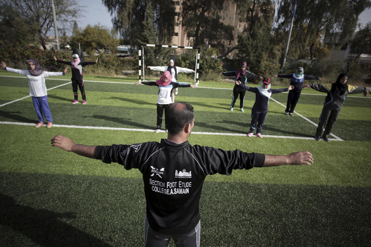 <p>Palestinian coach Mahmoud Tafesh leads warm-up exercises before a women's baseball game on a soccer field in Khan Younis, southern Gaza Strip, March 19, 2017. (Khalil Hamra/AP) </p>