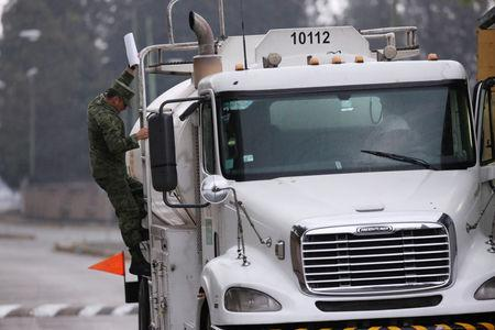 A Mexican soldier inspects a fuel truck before leaving a fuel distribution terminal in Mexico City, Mexico January 12, 2019. REUTERS/Daniel Becerril