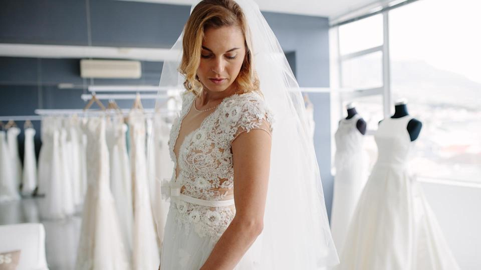 Beautiful young woman trying on bridal gown in wedding fashion shop.
