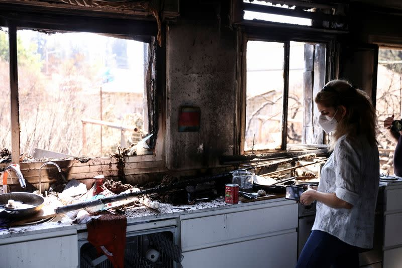 Dana Marcus, landlord of the house, inspects the place after it was damaged from wildfire in Givat Yearim