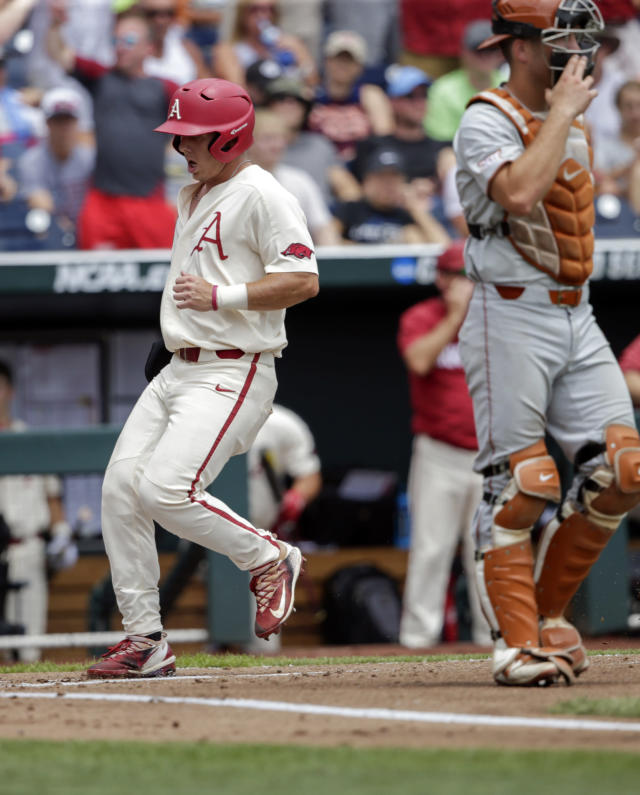 Arkansas' Eric Cole, left, scores on a single by Heston Kjerstad in front of Texas catcher DJ Petrinsky, right, in the first inning of an NCAA College World Series baseball game in Omaha, Neb., Sunday, June 17, 2018. (AP Photo/Nati Harnik)