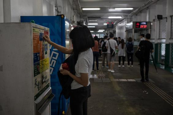 Gigi buys a token to take the ferry from Tsim Sha Tsui. She has opted not to use the prepaid transportation card to avoid being tracked (Nicole Tung/Washington Post)