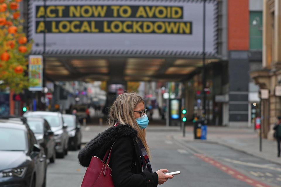 A woman wearing a face mask in Manchester city centre as the row over Greater Manchester's coronavirus status continues: PA